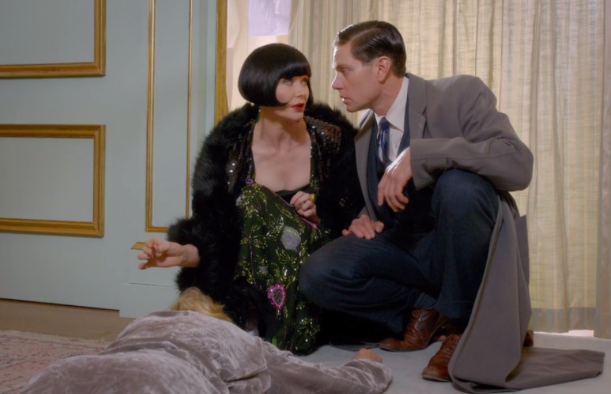 """Screenshot from Season Two, Episode 5, """"Murder a la Mode"""". Pictured is Phyrne Fisher, Lady Detective, and Detective Jack Robinson, (... and the murdered victim.)"""