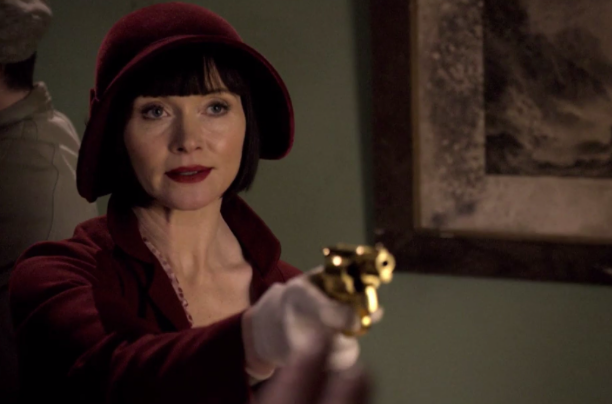"""Screenshot from Season One, Episode 1, """"Cocaine Blues"""". Pictured: Phyrne Fisher and her infamous gold gun, threatening a foe."""