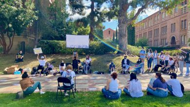 """Around 23 people sit and stand around a white screen at UCLA's Royce Quad during an accessibility protest. One person has their fist up and is holding up a sign that says """"Accessibility Now! We deserve better!"""" Two individuals are holding a disability pride flag. Kaplan Hall and Powell Library are visible in the background."""
